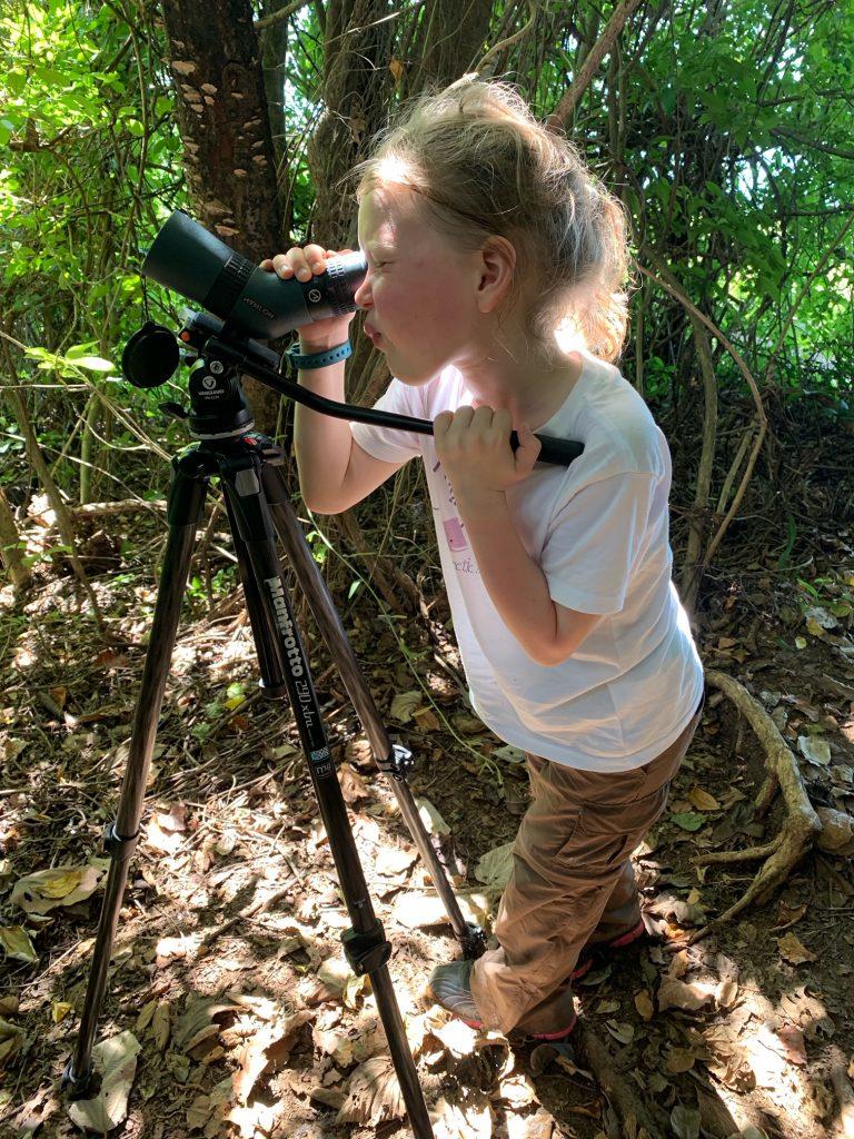 A girl look through a telescope at Samara Trails at Werner Sauter Biological Reserve near Playa Samara, Costa Rica