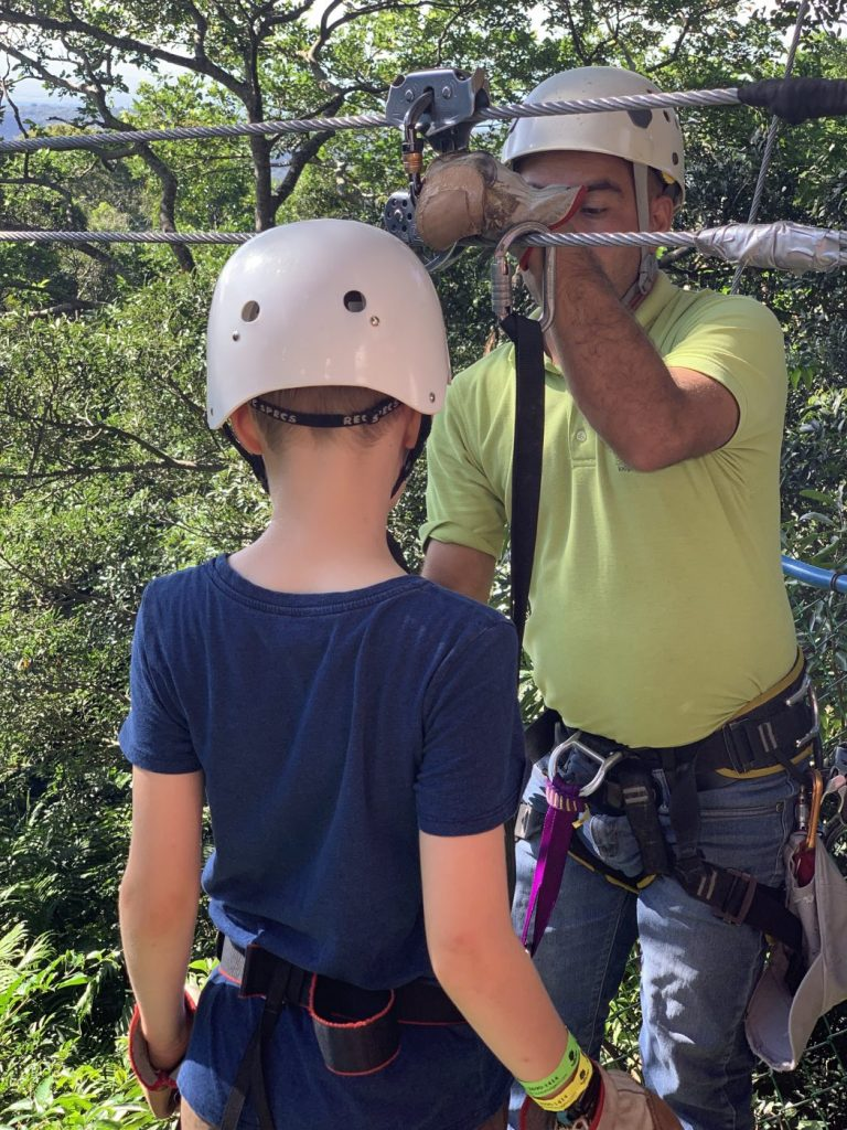 A kid and a guide preparing for a zipline at Buena Vista del Rincon