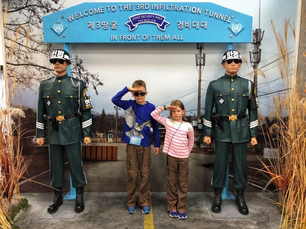Two children pose with fake soldiers at the DMZ - a top place to visit with kids in Seoul, Korea