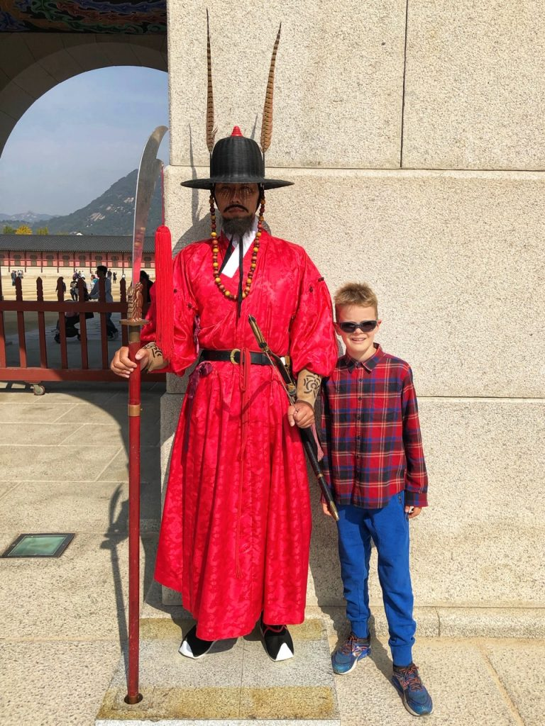 A boy posing with a Sumumjang (Royal Guard) at Gyeongbokhung palace - a top place to visit with kids in Seoul, South Korea
