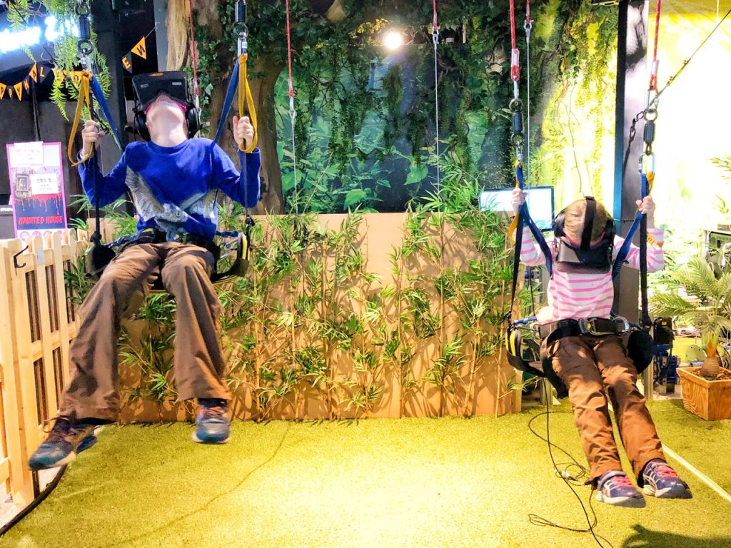 2 children on swings in a virtual reality cafe in Seoul, a top places to visit with kids