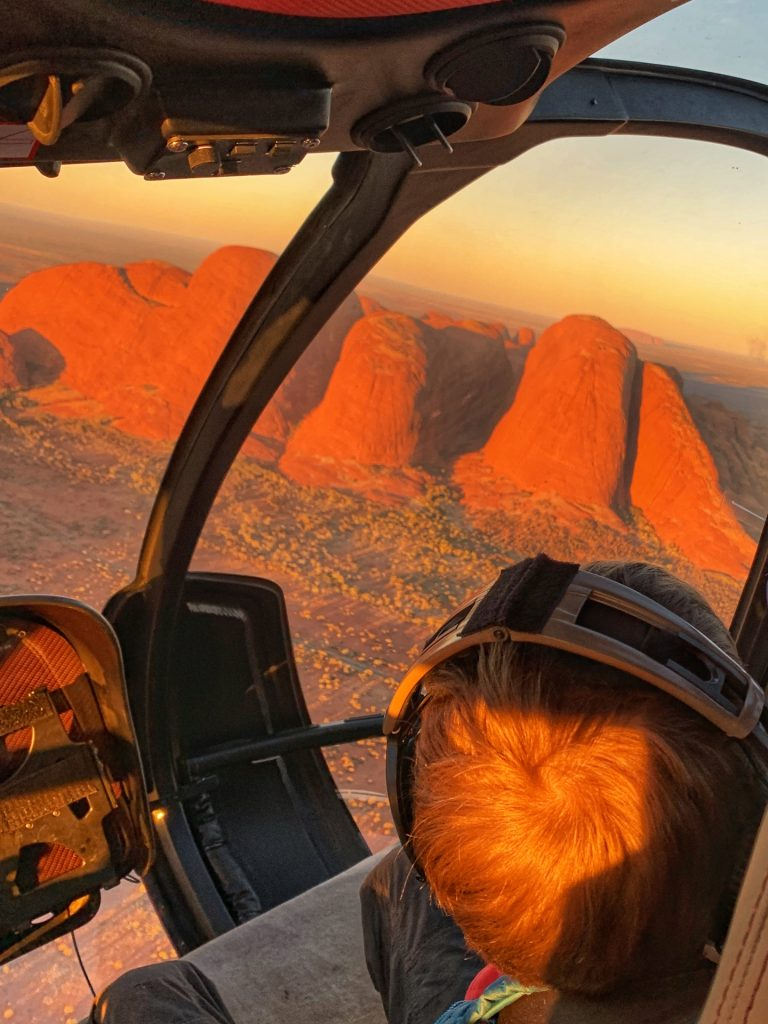Boy looking out a helicopter window at Kata Tjuta at sunset. A helicopter ride is one of the top things to do at Uluru.