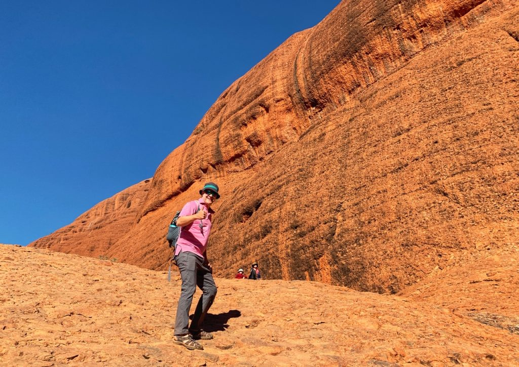 Man and two children hiking Valley of the Winds at Kata Tjuta.  Hiking at Kata Tjuta is one of the top things to do at Uluru.