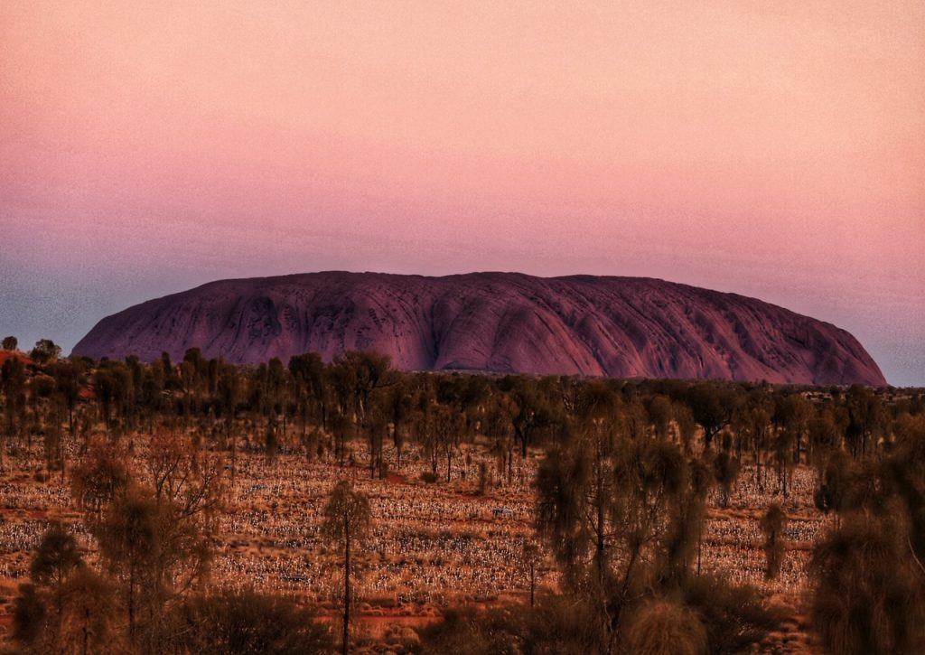 Uluru at sunset with the Filed of Lights in the foreground. A sunset at Uluru is one of the top things to do at Uluru.