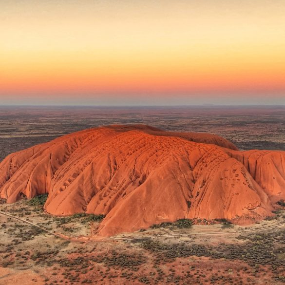 A sunset view of Uluru from a helicopter.