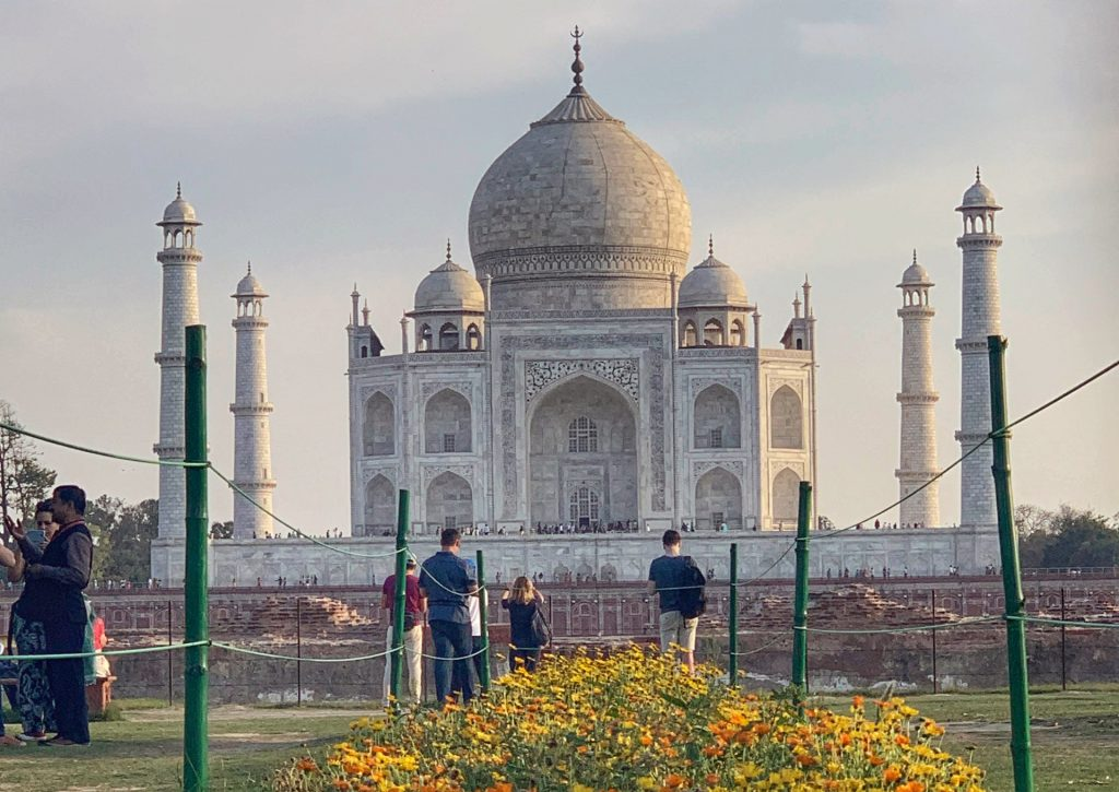 The Taj Mahal photographed at sunset from Mehtab Bagh with orange and yellow flowers in the foreground. Mehtab Bagh is a recommended stop on a one day visit to Agra.