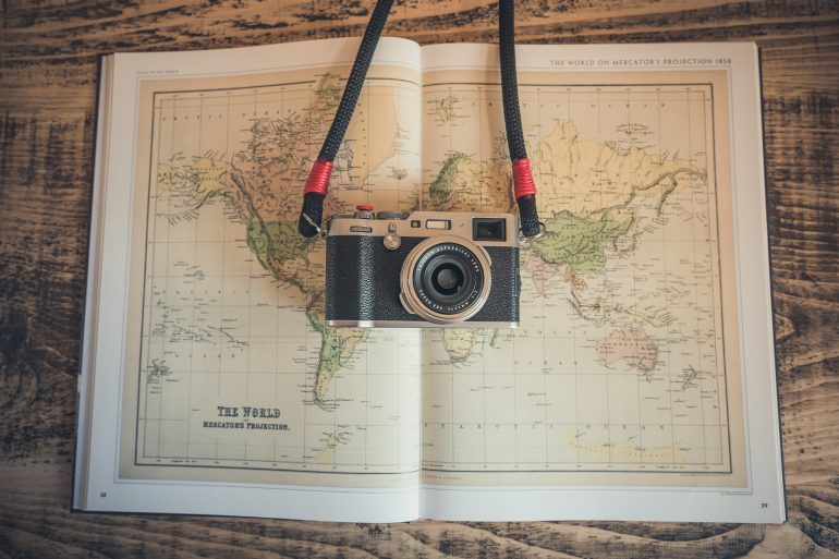 A camera laying on top of an atlas opened to a mercator projection of the world