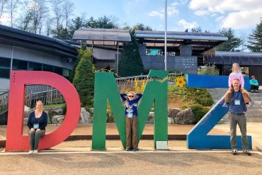 Family posing in large letters that spell DMZ while on a DMZ tour with kids in Seoul, South Korea