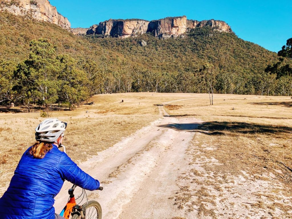 A woman mountain biking at Emirates One&Only Wolgan Valley