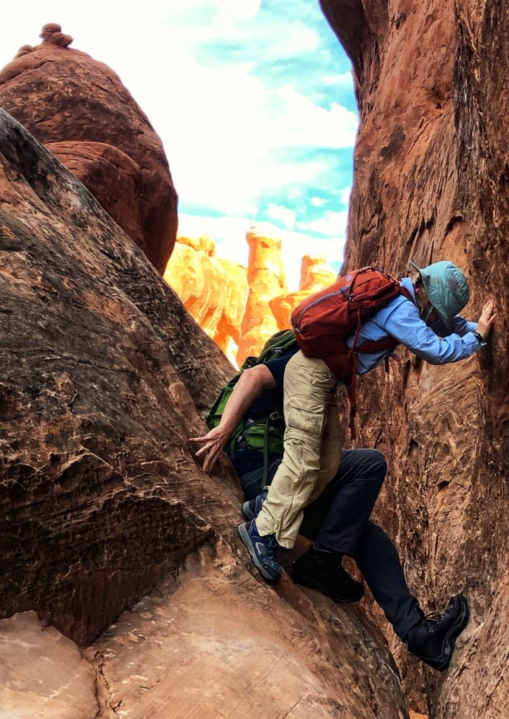 A father and daughter navigate a short climb in Fiery Furnace in Arches National Park.