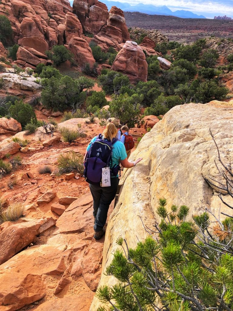 A mother and two children hiking towards Fiery Furnace in Arches National Park.