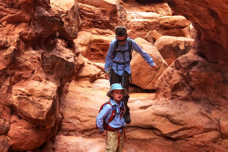 A girl and boy hiking under a sandstone arch in Fiery Furnace in Arches National Park.