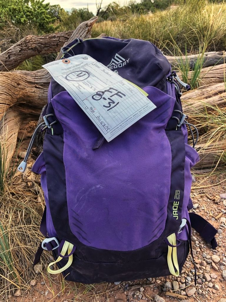A backpack with a permit attached for the Fiery Furnace hike in Arches National Park.