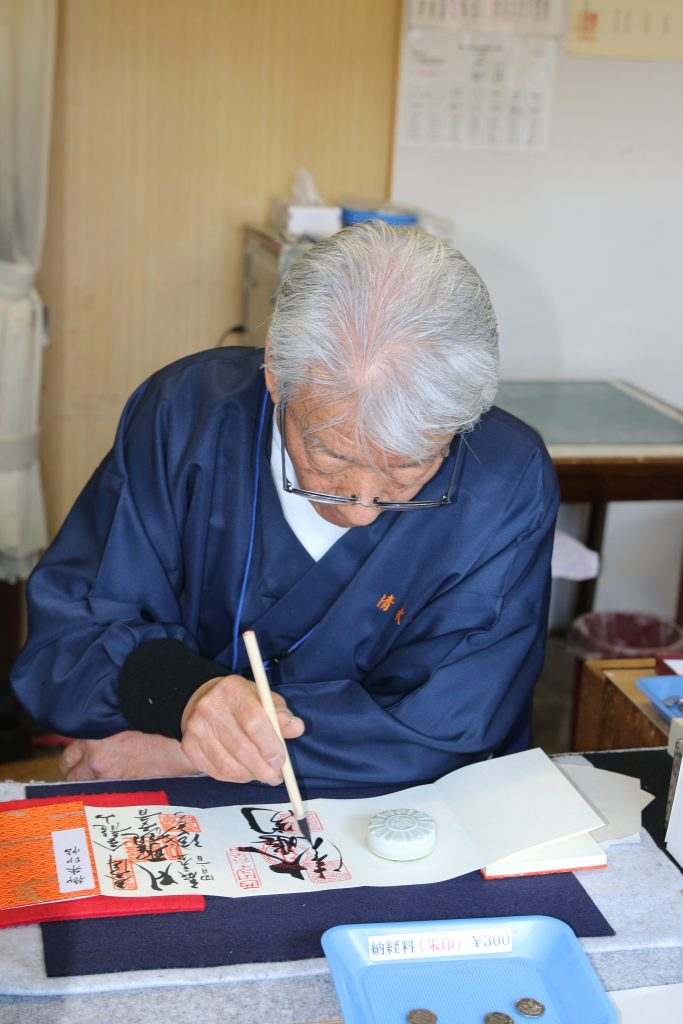 A monk completing the calligraphy on a goshuin.