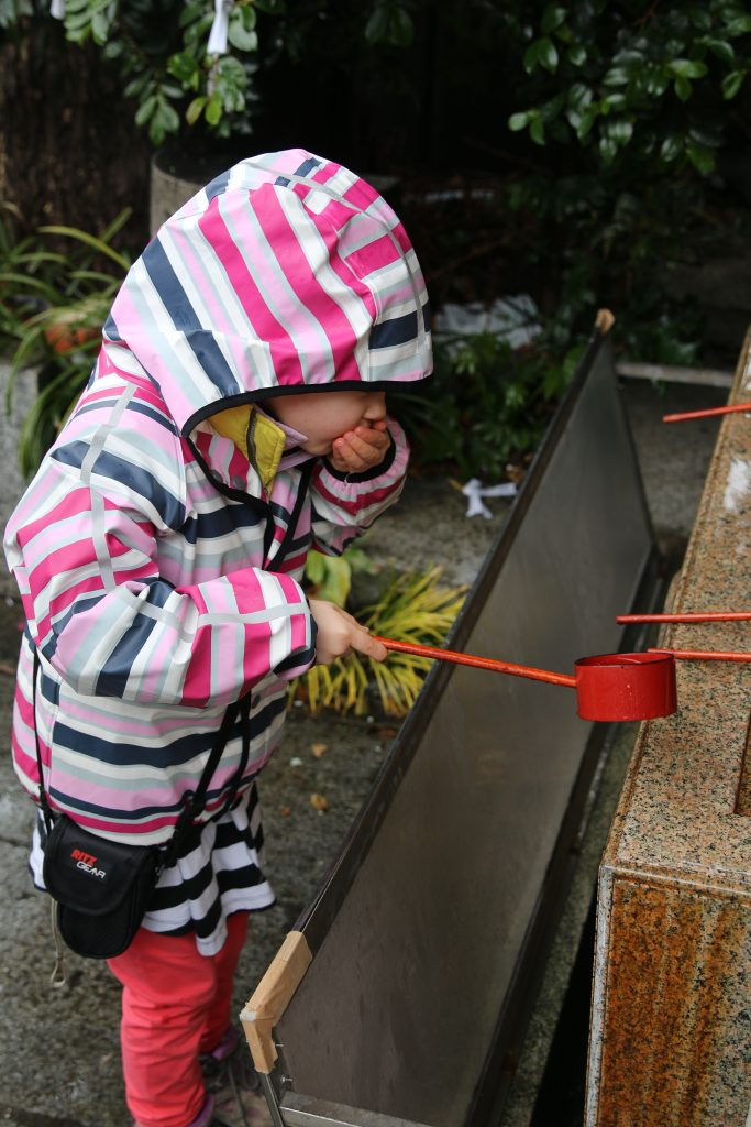 Girl rinsing her mouth as part of the ritual cleansing before praying at a Shinto shrine in Japan.