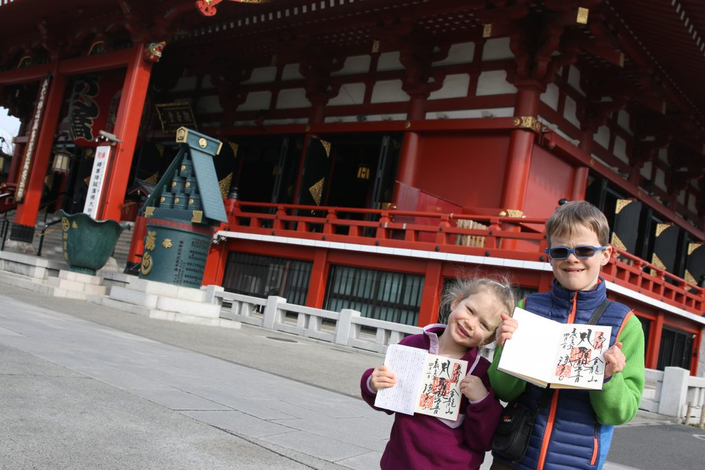 A girl and boy in front of Senso-ji holding goshuin-cho.