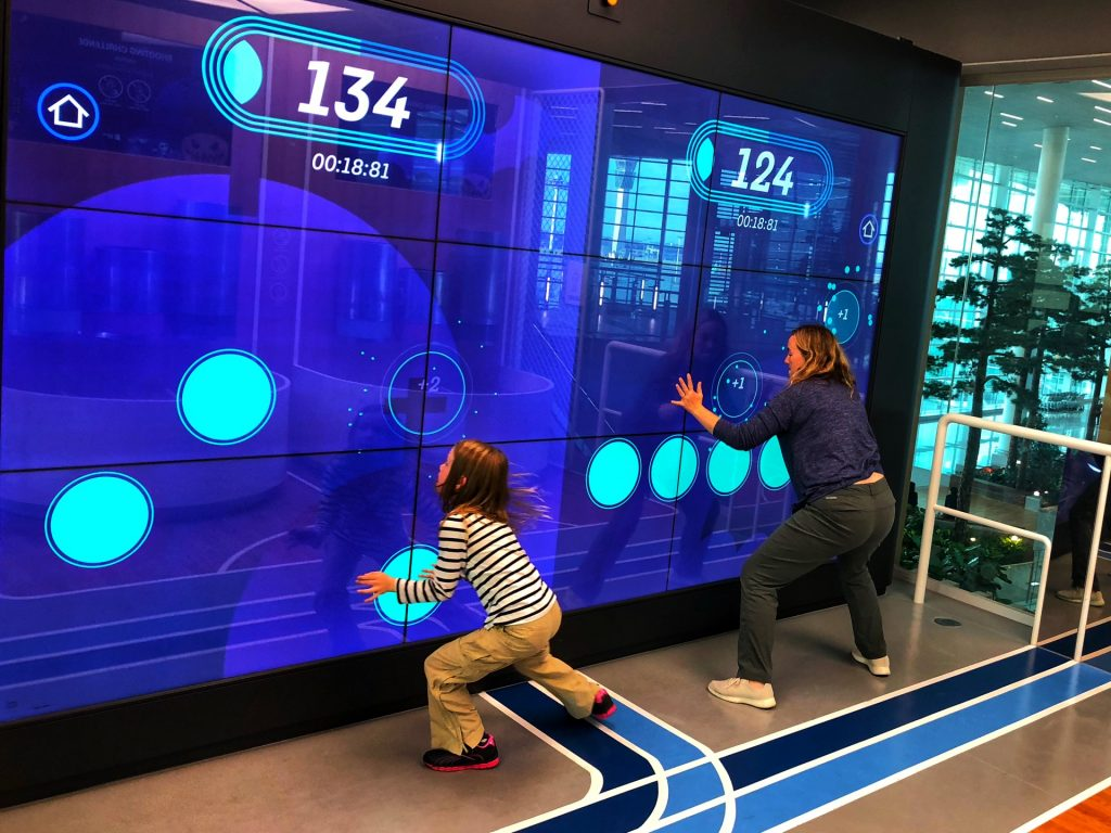Mother and daughter competing in the Digital Gym tech attraction at Seoul-Incheon International Airport.