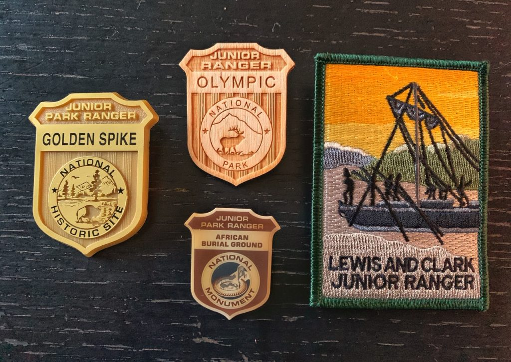 The 4 materials Junior Ranger badges are made from. A plastic badge from Golden Spike, a wood badge from Olympic, a metal badge from African Burial Ground, and a patch from Lewis & Clark