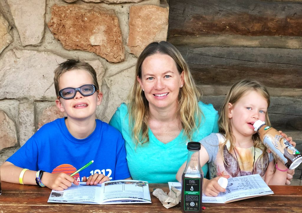 A mother and two children working on Junior Ranger program booklets at Grand Canyon National Park (North Rim)