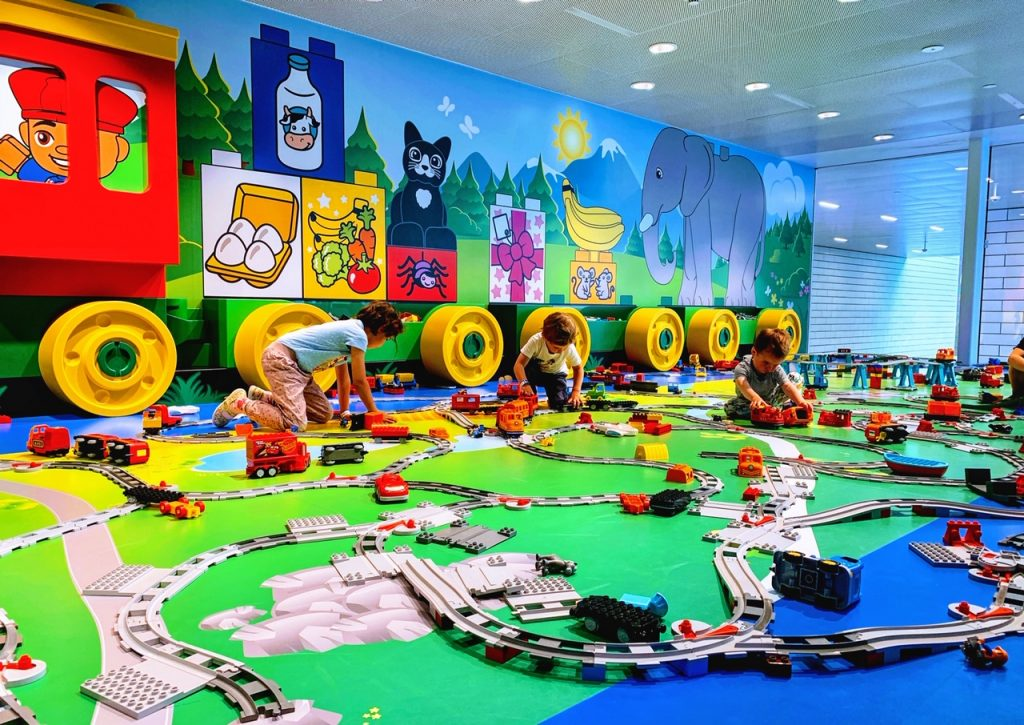 Children building with DUPLO trains in the Blue Zone at the LEGO House in Denmark