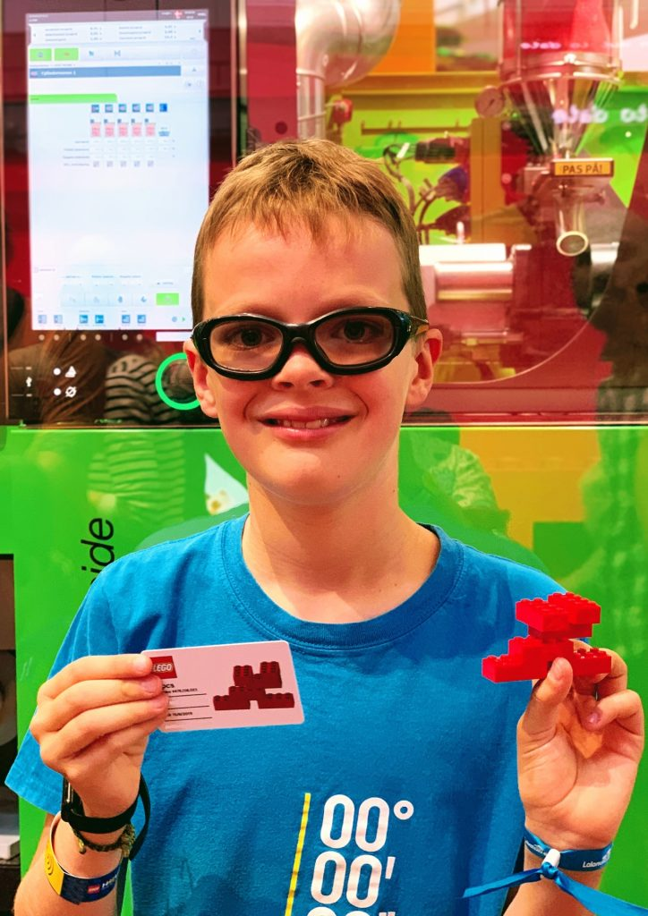 A boy holding a LEGO 6-brick combination and LEGO bricks from the LEGO House in Denmark