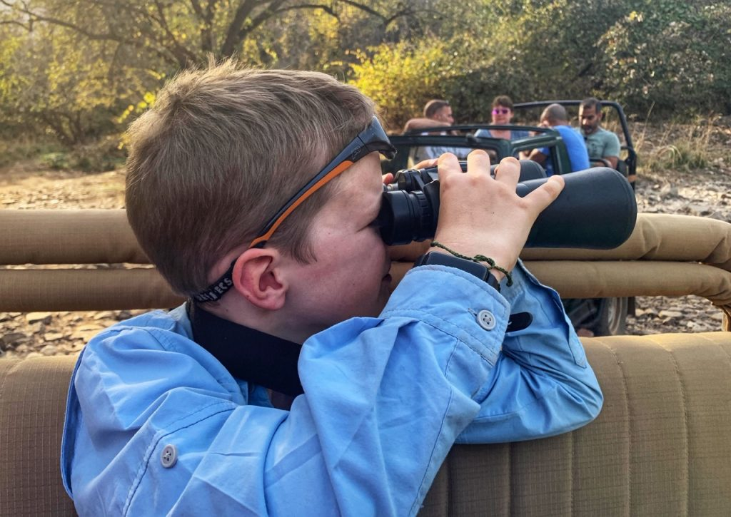 A boy looking through binoculars for Bengal tigers in Ranthambore National Park, India
