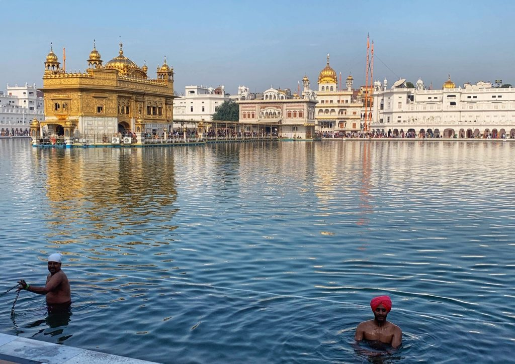 Bathing pilgrims at the Golden Temple (Sri Harimandir Sahib) in Amritsar, India. The Golden Temple is a top thing to do in Amritsar.
