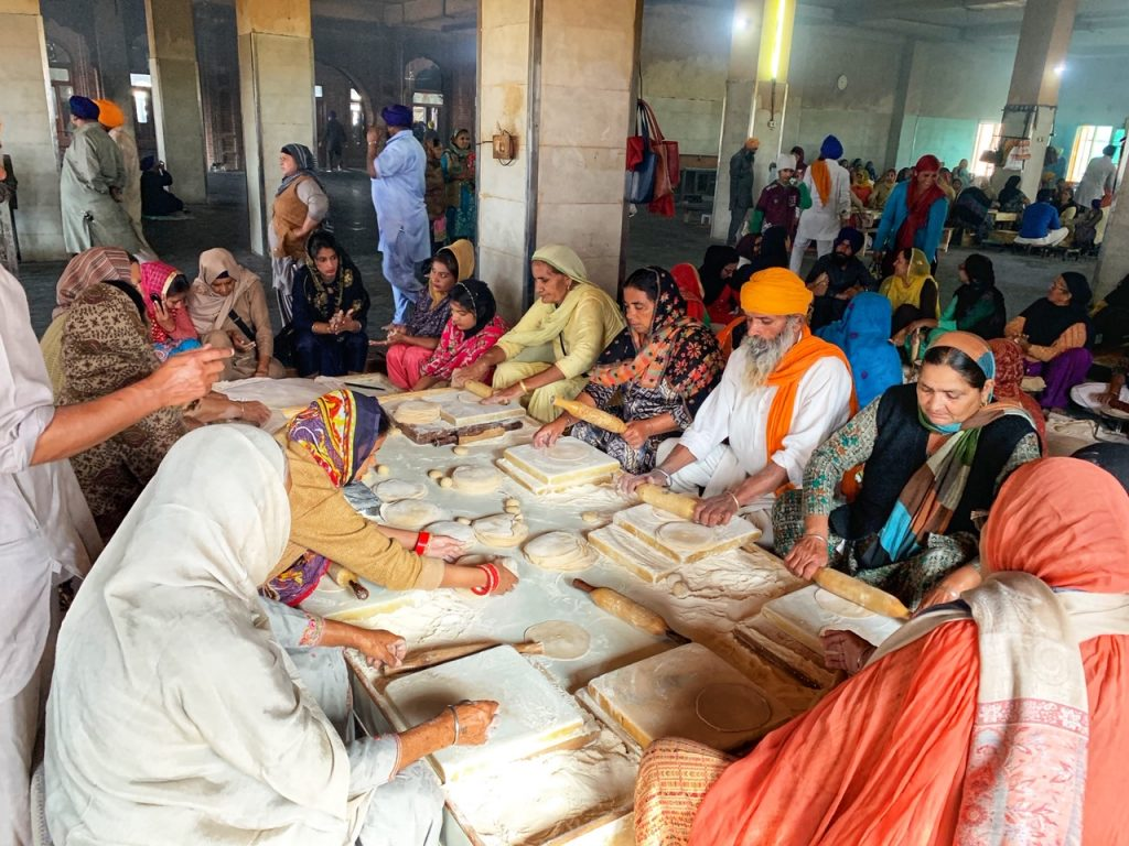 A group of people prepare chapatis in the community kitchen (langar) at the Golden Temple in Amritsar, India. A top thing to do in Amritsar.